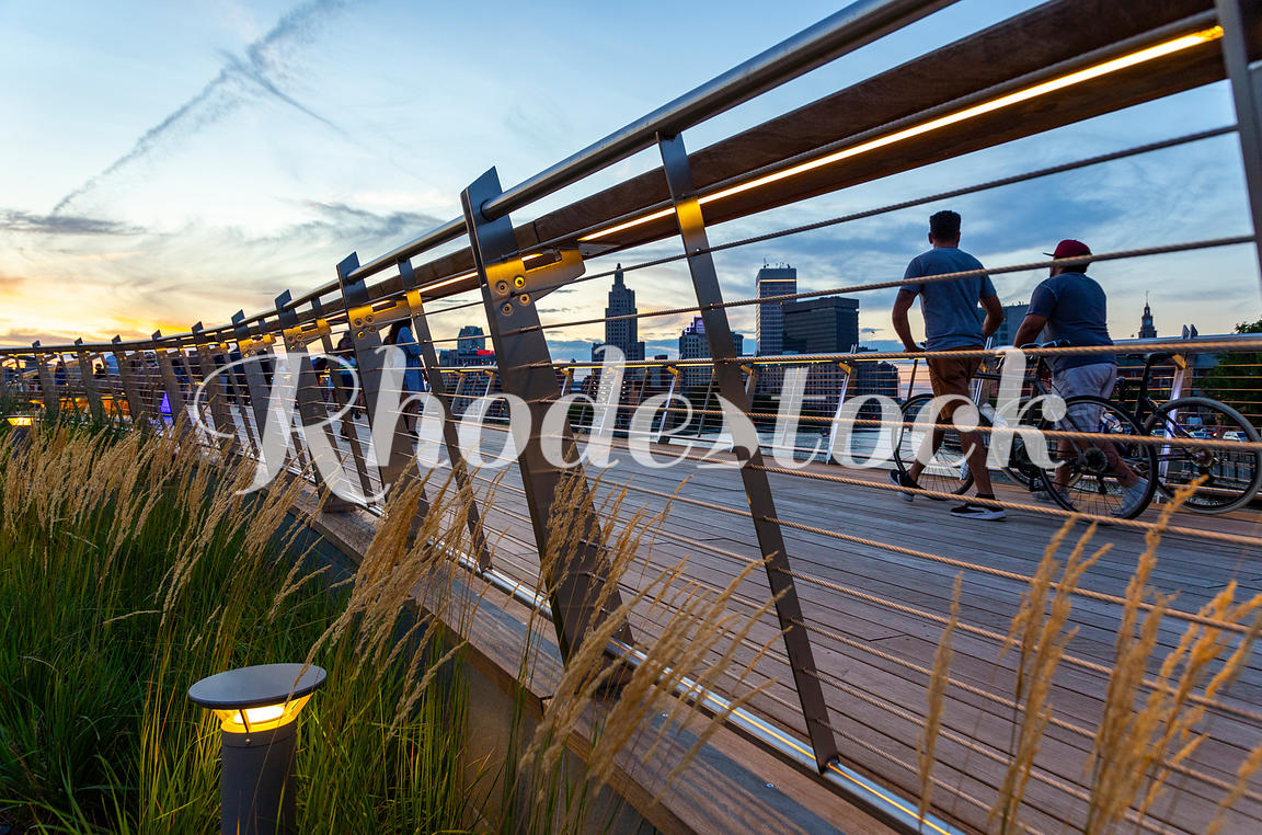 People walking their bicycles on the Providence River pedestrian bridge at sunset