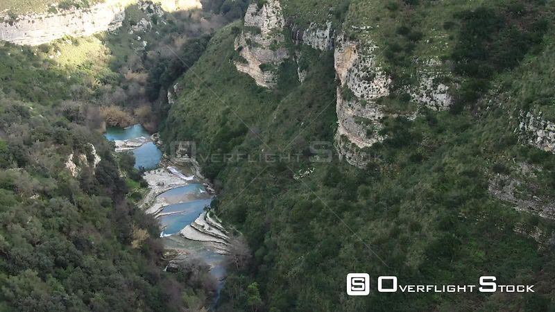 Aerial push out view of a small river at the bottom of a canyon in Cavagrande Sicily. Italy