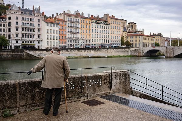 Lonely elderly man stands along the edge of the Saone River pondering life in Lyon, France