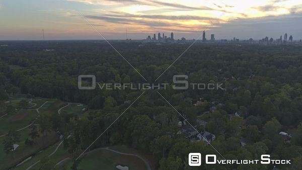Atlanta Panoramic cityscape at sunset flying above gold course with skyscraper skylines and trees