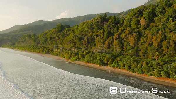 Flying low over ocean waves and beach panning with jungle views. Costa Rica