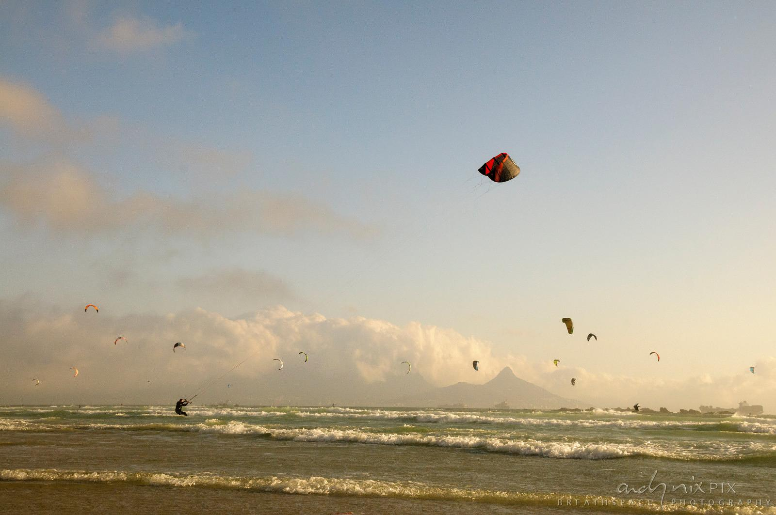 Many kitesurfers on sea with Table Mountain in background