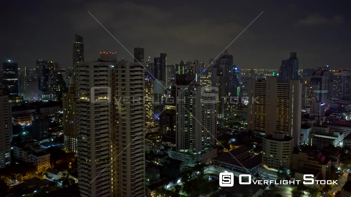 Bangkok Thailand Hyperlapse flying backwards out of downtown skyscrapers in Watthana district at night