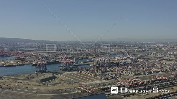 Long Beach CA Flying toward suspension bridge overtop working shipyard port industrial cityscape