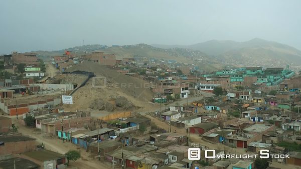 Ventanilla  Peru  Flying low over urban poverty hillside housing area then panning down.