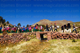 Aymara people walking along a raised section of the Qhapaq Ñan Inca road where it crosses a stream between Azafranal and Titi...