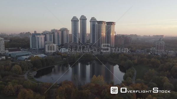 Autumn Sunset Forward Flying Over the Pond Towards Modern Residential Buildings. Moscow Russia Drone Video View