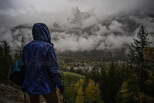Woman with a hood looks out over downtown, Chamonix and the French Alps