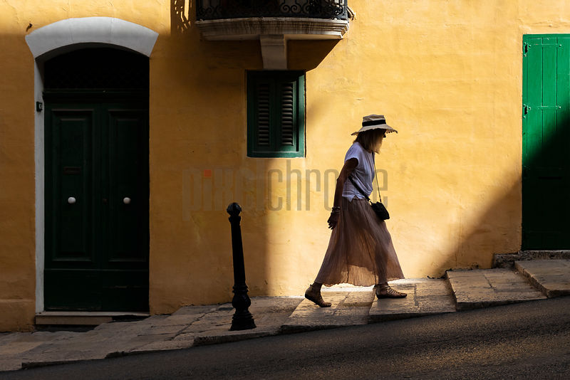 Woman in a Hat Walking up Republic Street in Old Valletta
