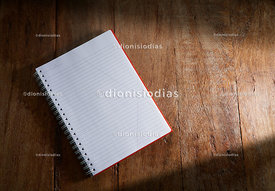 Open notebook on wooden background.