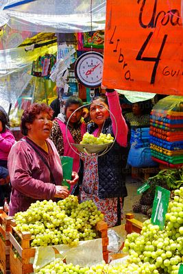 Woman buying grapes in market on New Year's Eve, La Paz, Bolivia