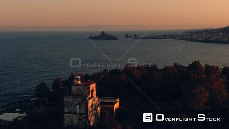 Aerial approaching view of a lighthouse at sunset in the East coast of Sicily. Italy