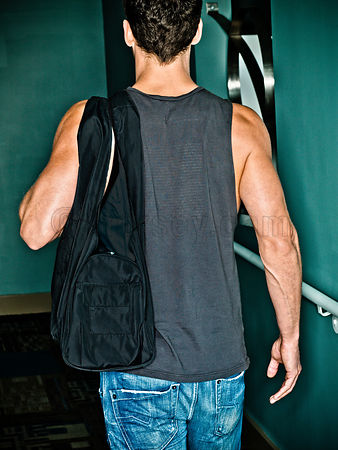 image of male from behind walking down a halway with a black gym bag over one shoulder