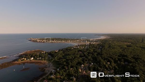 Flying over coastline homes panning at sunset with views of York. Maine