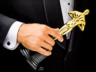 Close-up of a male's hand holding an award, dessed in a tuxedo.
