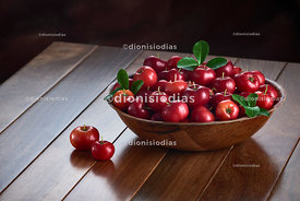 Fresh acerolas in a wooden pot on wooden background.