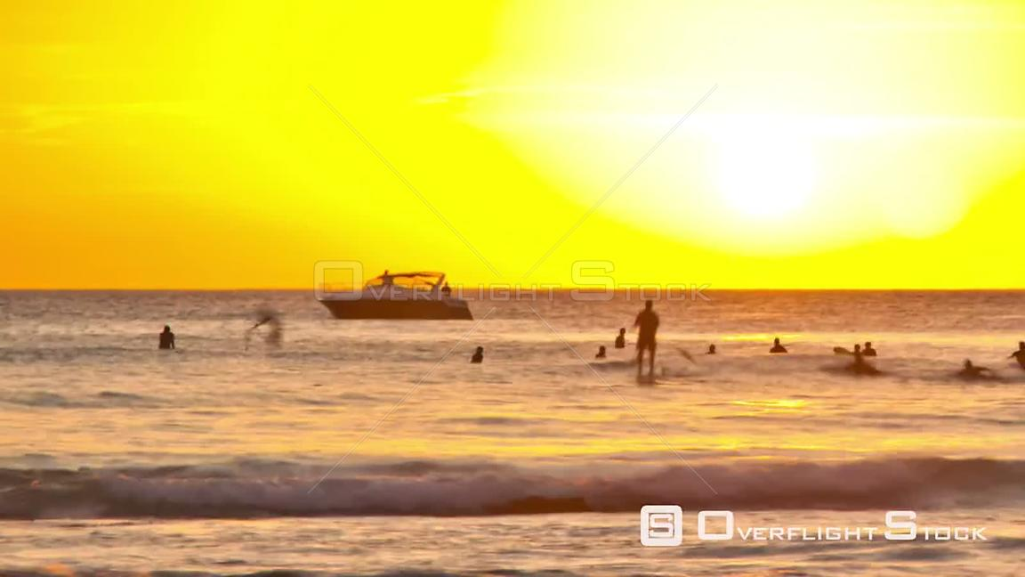 Beach time lapse clip of surfers and boats going by during sunset. Hawaii