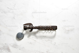 Vintage bottles opener with bottle cap on white marble background.