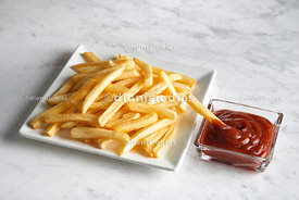 French fries in a diagonal square dish with potato in a ketchup pot