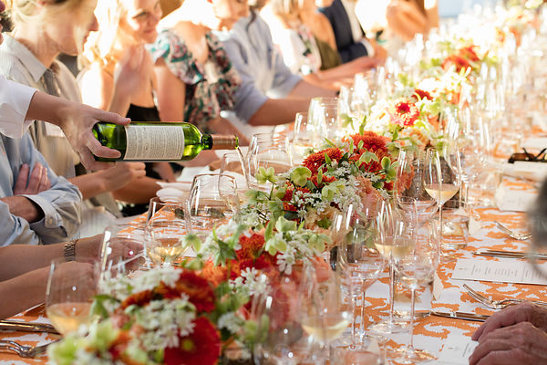 Guests sitting at a long festive table at a summer party.