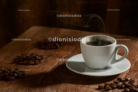 Coffee cup on wood background with roasted grains selected horizontally.