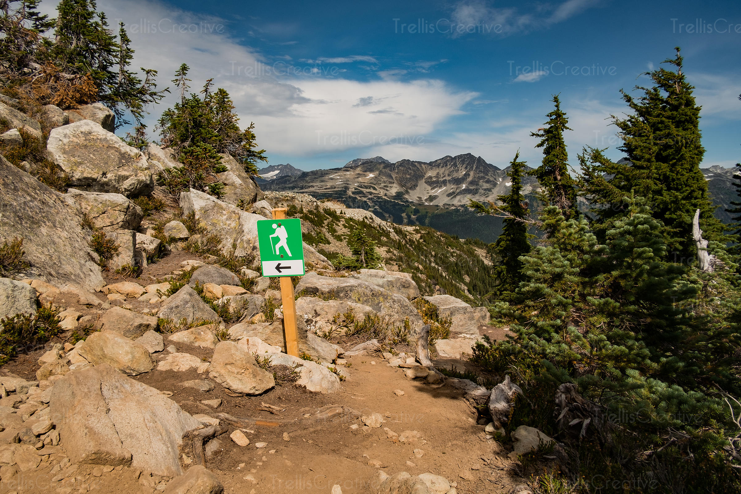 Trail marker on rugged hiking trail leads the way, Blackcomb Mountain, Whistler, Canada.