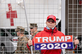 "March 30. 2020 - New York, New York - Man holding a ""Trump 2020"" banner at the gates of the 1,000-bed floating hospital, USNS..."