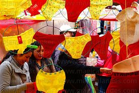Young women shopping at stall selling red and yellow underwear on New Year's Eve, La Paz, Bolivia