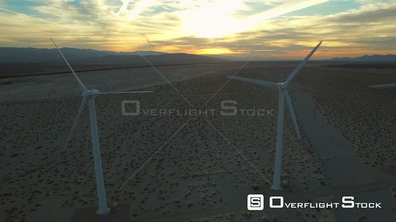 California USA  Flying low side view along large wind turbines at sunrise.