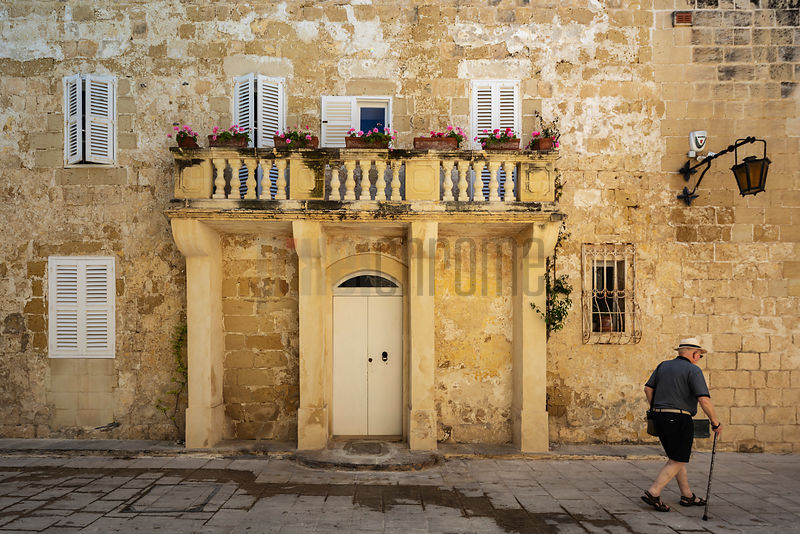Man with a Cane Walking in Front of a House in the Walled City