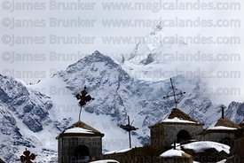 Crosses and tombs  in Milluni cemetery after winter snowfall, Mt Huayna Potosi in background, Cordillera Real, Bolivia