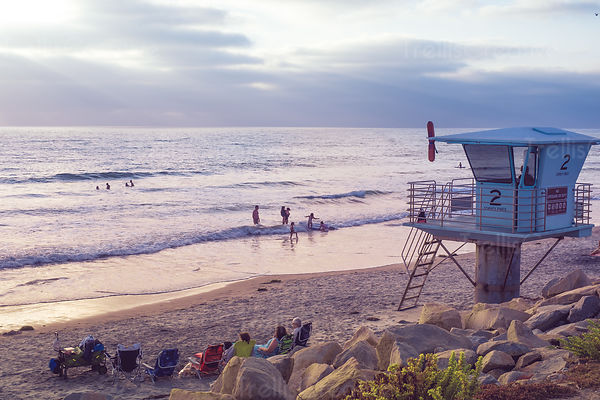 Sunset over lifeguard station and people on beach at Torrey Pines State Preserve, San Diego, California, USA.