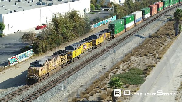 Freight Train Along Side Warehouses and Industry.