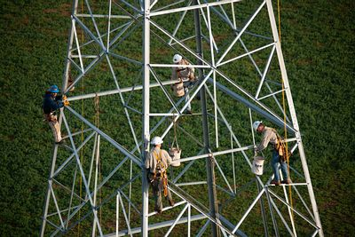 Aerial photograph of workers constructing a transmission tower
