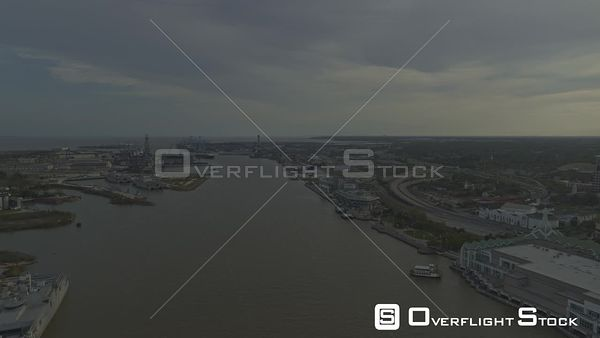 Mobile Alabama Flying low over industrial river area with downtown cityscape views at sunset
