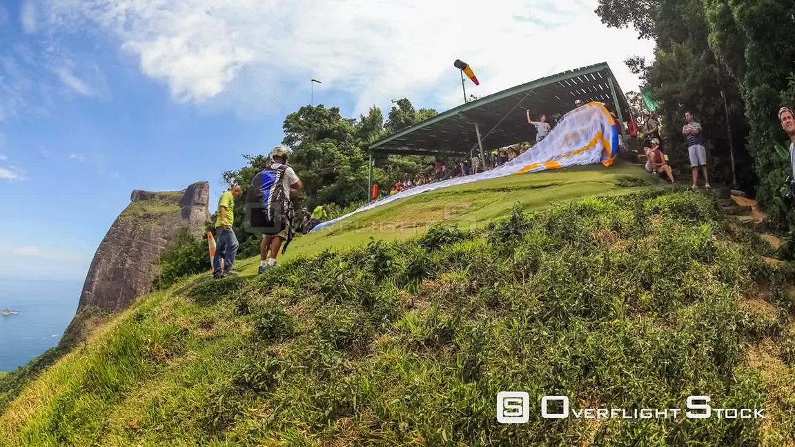 Panning time lapse of hang gliders and para gliders taking off from hillside in Rio De Janeiro, Brazil