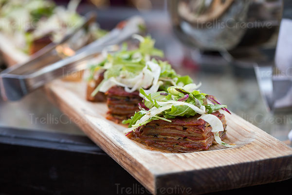 Wooden platter of cooked food with salad garnish.