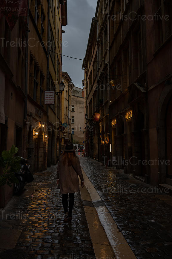 Following a woman walking along Lyon's cobblestone street