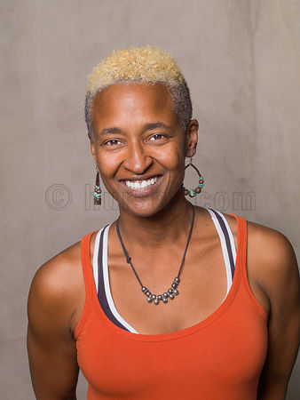 Image of an African American Woman against a textured wall in an orange tank top with short bleached hair and a big smile.