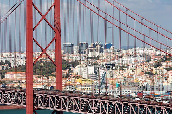 A Plane takes off from Lisbon Airport as seen through the Ponte 25 de Abril Suspension Bridge