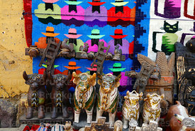 Bull statues, wooden crosses and weavings for sale outside shop, Ollantaytambo, Sacred Valley, Peru