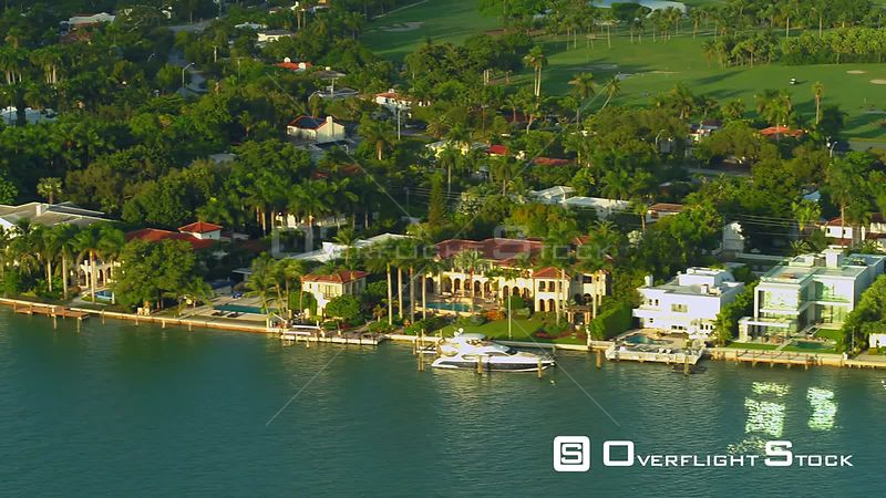 Aerial stock Miami Beach waterfront real estate house mansions golf course view 4k