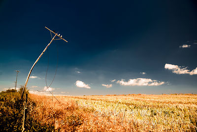 Bendy broken telephoone pole with loose wires next to a dry field of cut wheat