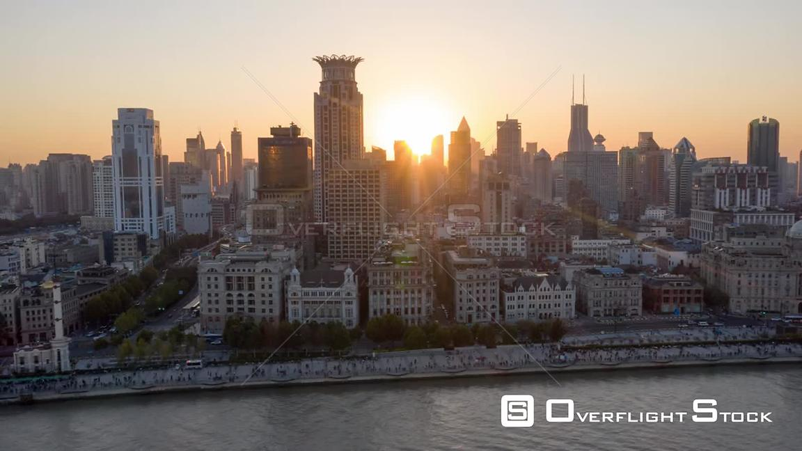 China Shanghai Aerial Hyperlapse flying low over Huangpu river with waterfront & sunlight glare in view, pedestrians