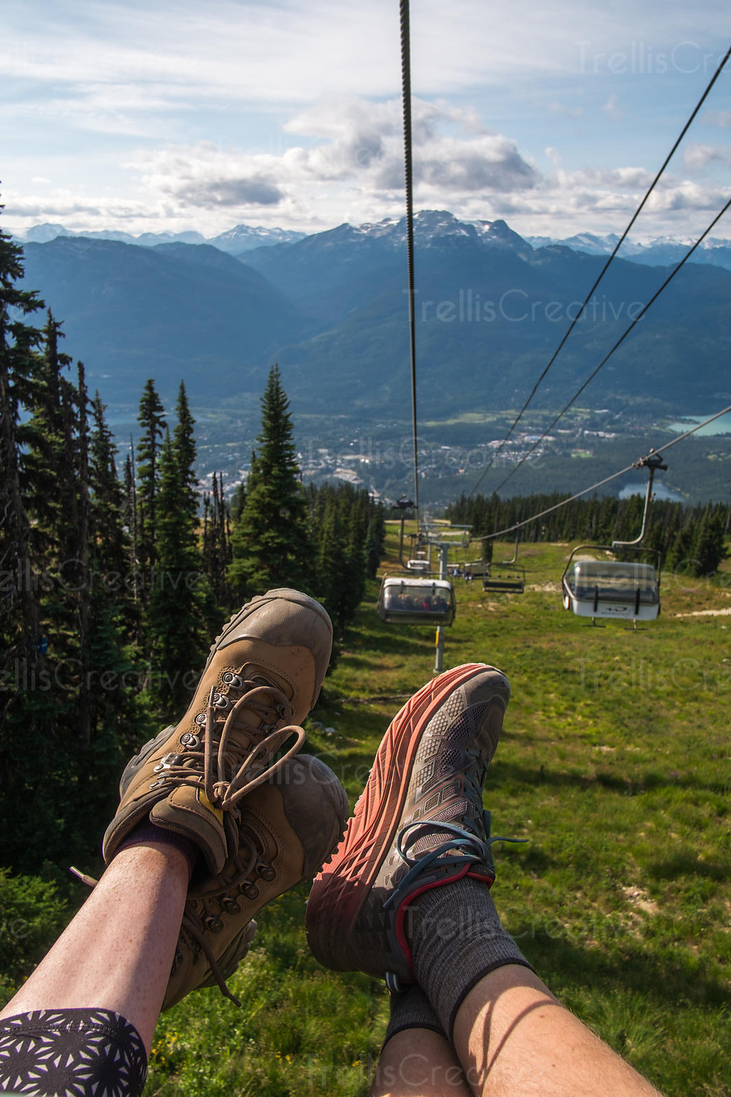 Two people riding chair lift down Blackcomb Mountain, Whistler, Canada.
