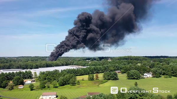 A pillar of black smoke rising from a barn fire in a rural part of Maryland