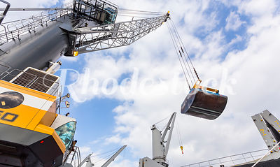 A Crane Swings a Shovel Bucket While Unloading Cargo Ship