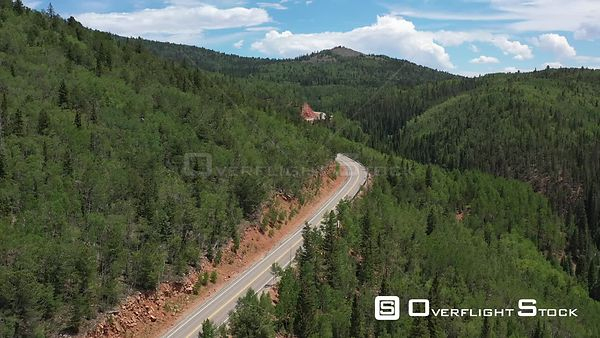Tree covered mountain peaks and valley, and a winding road, Teller County, Colorado, USA