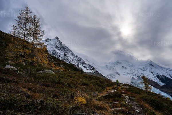 A backpacker hikes along rocky trail leading to a mountain glacier in the Alps
