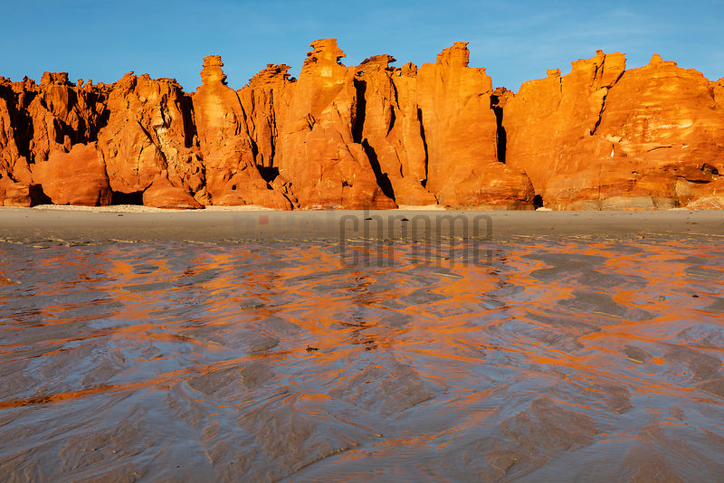 Sandstone Cliffs Reflected on Beach